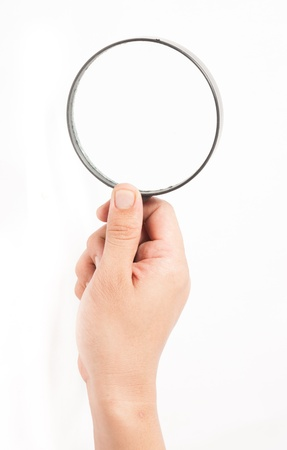 Magnifying glass in hand isolated on white background photo