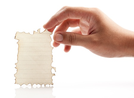 Hand holding piece of burned paper on white background. Stock Photo - 21529550