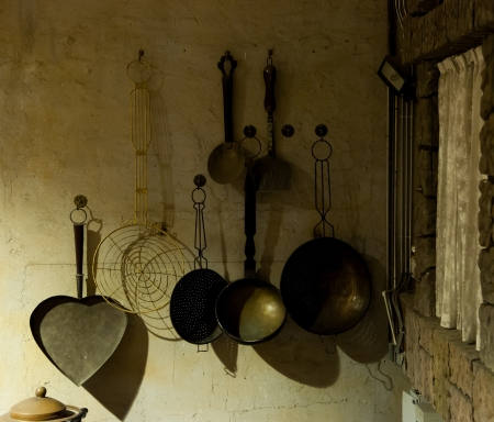 the old times: kitchenware hanging in the kitchen of an old country house - retro equipment of old times