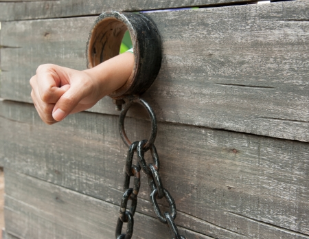 Locked Up hand is shackled to a vintage prison cell door with a ball and chain photo