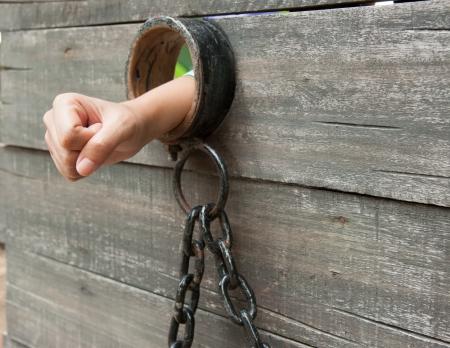shackled: Mano Locked Up est� encadenado a una puerta de celda vintage con una bola y una cadena
