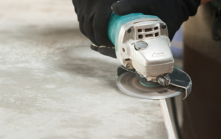 grinder worker cuts a stone the electric tool worker is tiling at home, tile photo