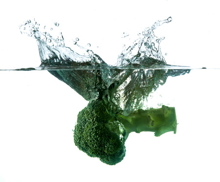 twirling: Green broccoli falling in water on white with air bubbles