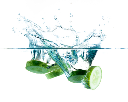 sliced cucumbers splashing water isolated on white photo