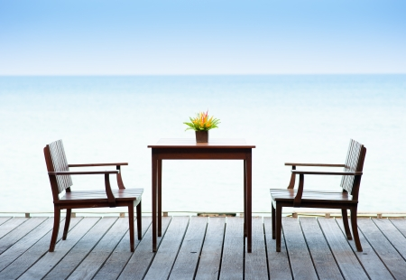 Terrace sea view with outdoor wood chairs and table photo