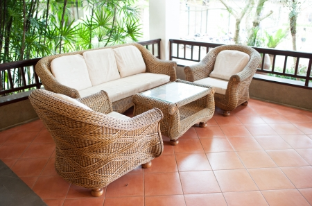Home exterior patio with wooden decking and rattan sofa