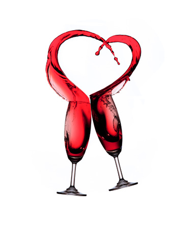 Heart splash from two glasses of red wine isolated on white background photo
