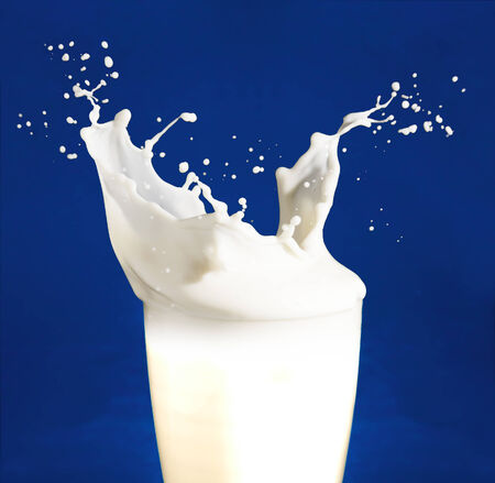 milk splash: Splash of milk from the glass on a blue background
