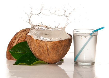 green water: Coconut with water splash over white