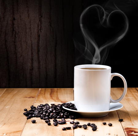 Cup of coffee with fume on the wooden background photo