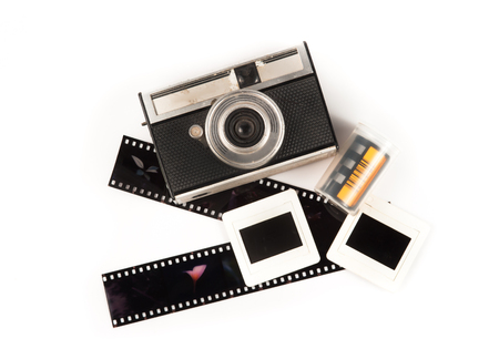 old camera and blank film strip on White background photo
