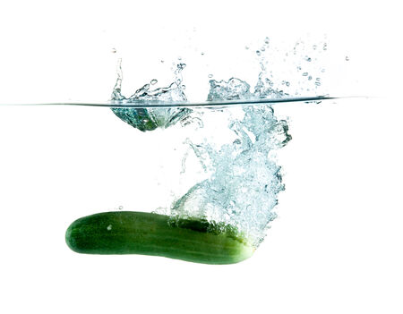 green cucumbers dropped into water isolated on white photo