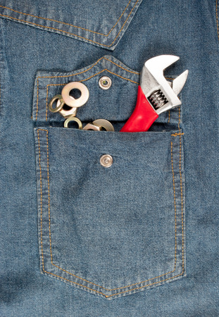 closeup of an adjustable wrench in a jean pocket photo