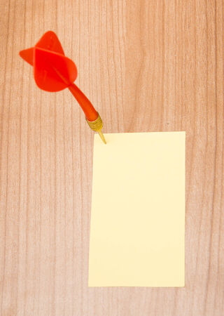 memorise: Red darts in an empty or blank notepad on a vintage wooden board