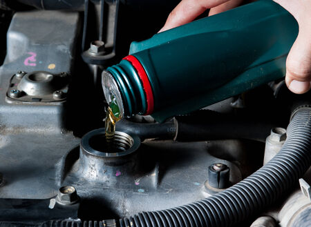 Car mechanic changing engine oil photo