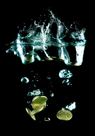 coins falling down to water photo