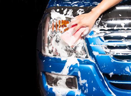 man het wassen van een zeepachtige blauwe auto met een roze spons.