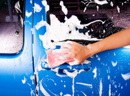 hand hold sponge over the car for washing photo