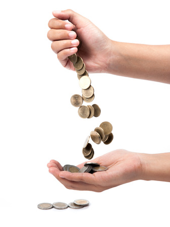 hand pour down coins into hands of another person. photo
