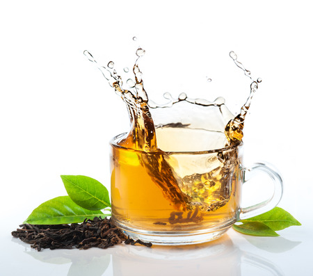 limpid: glass cup of tea withsplash out Stock Photo