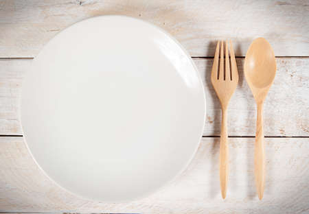 plate with fork and spoon on white wood photo