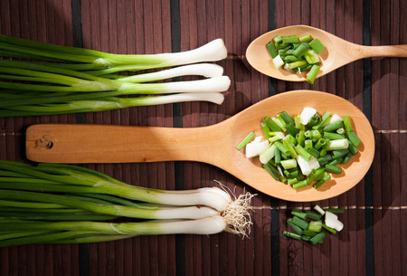 Chopped green  onions and spoon on a wooden photo