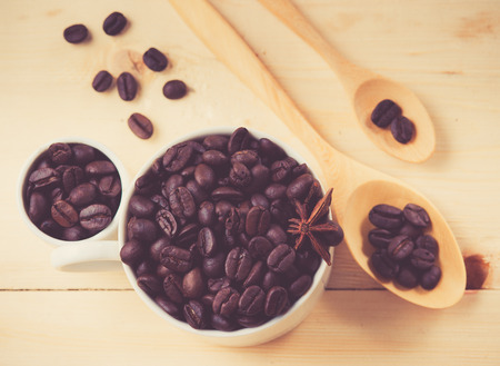Coffee beans in cup on wood background,selective focus, retro filter effect photo