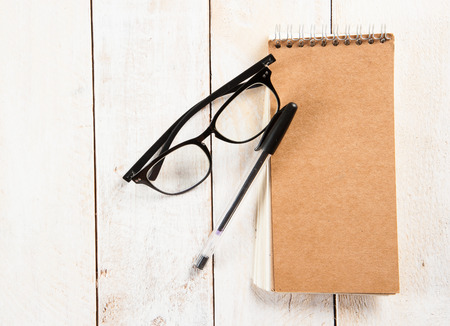 notepad,glasses and ink pen on the wooden photo