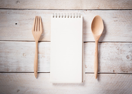 blank recipe book with wooden spoon, vintage toned photo