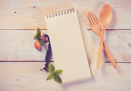 Cookery book and wooden spoon on wooden background, vintage toned photo