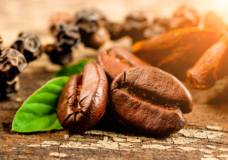 Coffee grains and green leaf on grunge wooden background photo