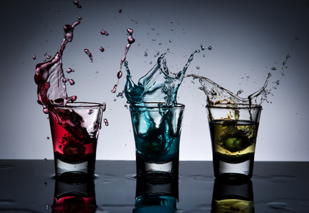 Splash of alcohol cocktail and glass ,dark background photo