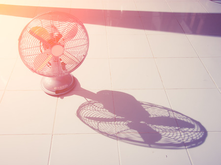 hot cold: vintage Antique fan and shadow on tiled floor