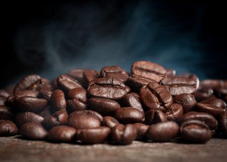 Coffee beans roasting with smoke Imagens