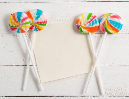 card with lollipops and on white wood photo