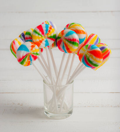 Colorful spiral lollipops on white wood photo