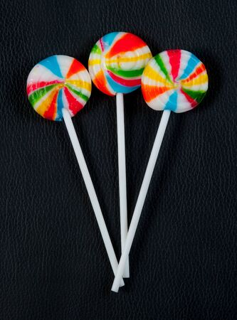 lolly pop: Colorful spiral lollipop lolly pop on black leather Stock Photo