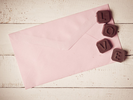 Chocolate heart with letter paper on the wooden background,vintage color toned image photo