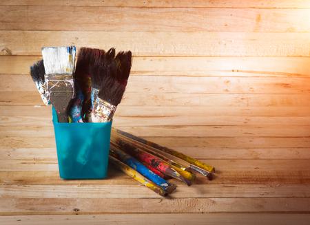 Used artist paintbrushes on wood background photo