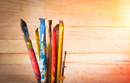 paintbrushes: Used artist paintbrushes on wood background