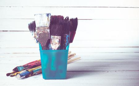 Used artist paintbrushes on wood background,vintage color toned image photo