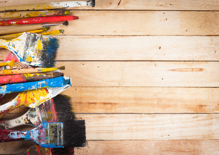 Used artist paintbrushes on wood background photo