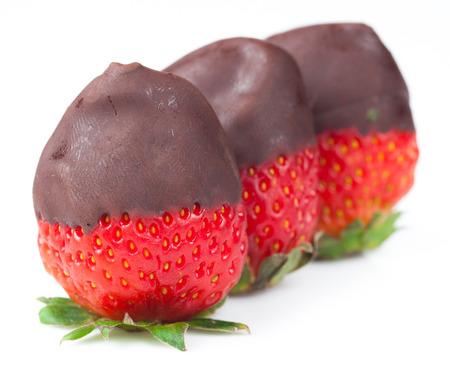 Row of strawberries dipped in delicious chocolate isolated on white photo