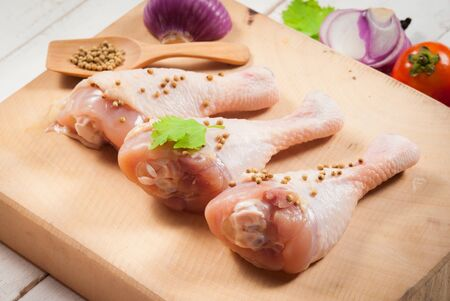 Raw Chicken Drumsticks with parsley and pepper on cutting board photo