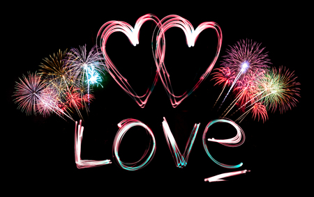 Love and heart made from light and fireworks on black background. photo