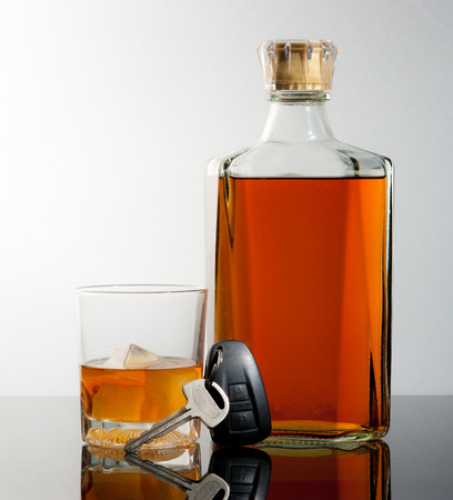 Glass of whiskey and car keys on gradient background photo