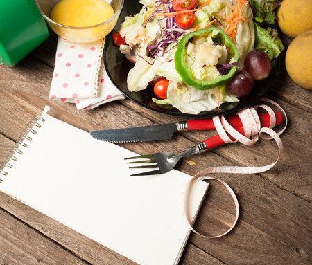 Fresh healthy salad and notepad on wooden table. View from above photo