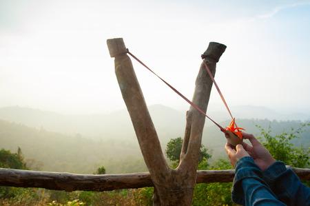 pull toy: Mano honda tirando tiro Prepar�ndose para el disparo de la semilla del �rbol en el bosque Foto de archivo