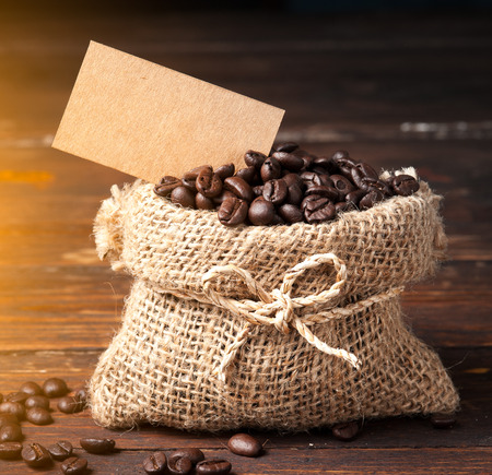 Coffee beans in bag and paper note for text on wooden table photo