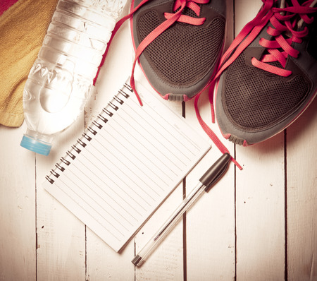 sports activities: Set for sports activities and notebook on white wooden background,vintage color toned image